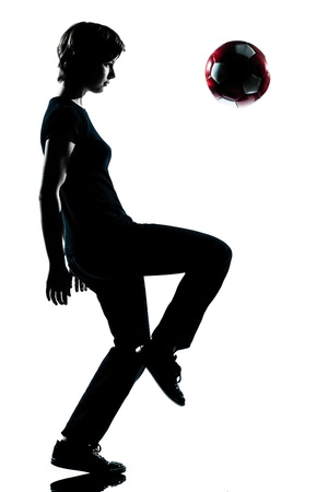one caucasian young teenager silhouette boy   juggling soccer football full length in studio cut out isolated on white background photo