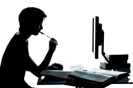 one caucasian young teenager silhouette boy or girl studying with computer computing laptop in studio cut out isolated on white background Zdjęcie Seryjne