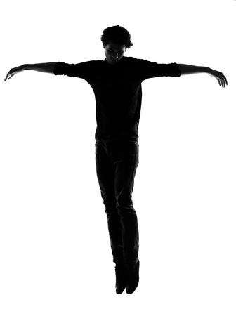 levitation: young man silhouette in studio isolated on white background