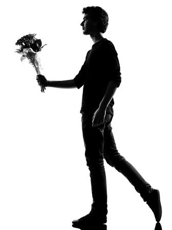 couple lit: young man offering flowers bouquet silhouette in studio isolated on white background