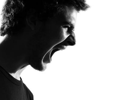 enojo: hombre joven gritando silueta retrato enojado en el estudio aislado sobre fondo blanco Foto de archivo