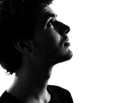 young man looking up portrait silhouette in studio isolated on white background photo