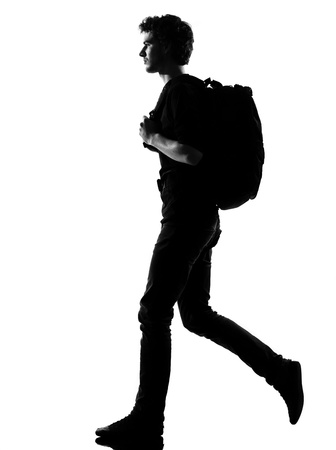 backpackers: young man backpacker walking silhouette in studio isolated on white background Stock Photo