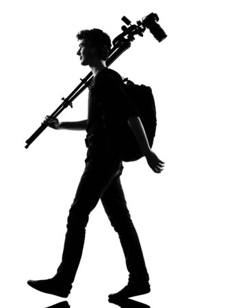 backpacking: young man photographer silhouette in studio isolated on white background