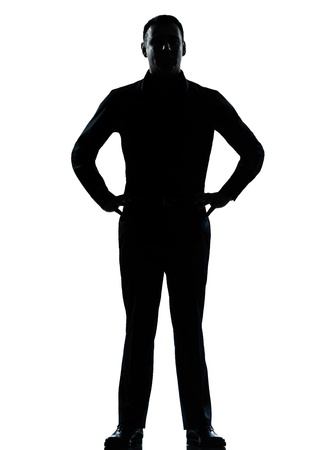 standing out: one caucasian business man silhouette standing hands on hips Full length in studio isolated on white background