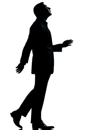 one caucasian business man walking looking up silhouette Full length in studio isolated on white background photo