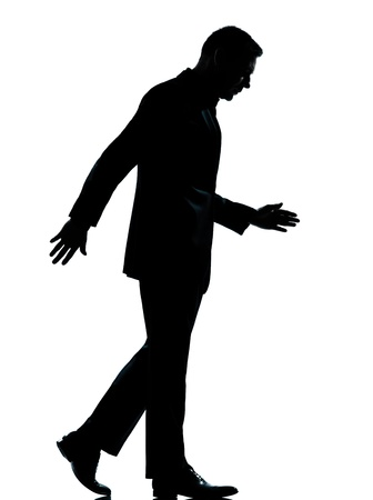 walking down: one caucasian business man walking silhouette Full length in studio isolated on white background