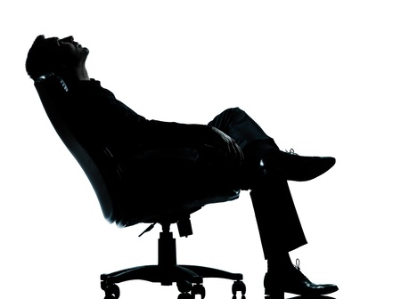 one caucasian business man relaxing thinking sitting in armchair silhouette Full length in studio isolated on white background Stock Photo - 13339195