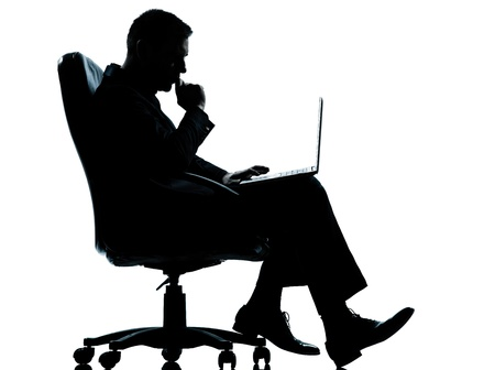 caucasianos: one caucasian business man computer computing serious sitting in armchair silhouette Full length in studio isolated on white background Banco de Imagens