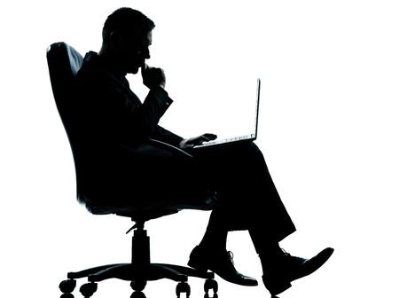 usando computadora: un hombre cauc�sico de negocios equipo de computaci�n sesi�n seria de largo silueta completa sill�n en el estudio aislado sobre fondo blanco Foto de archivo