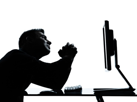begging: one caucasian business man computer computing begging despair silhouette in studio isolated on white background Stock Photo