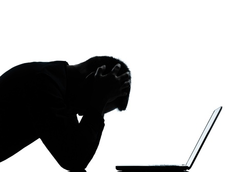 one caucasian business man computing computer laptop despair sad portrait silhouette in studio isolated on white background Stock Photo - 13339197