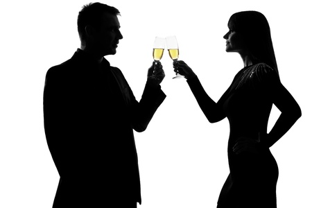 couple lit: one caucasian couple man and woman drinking champagne toasting partying in studio silhouette isolated on white background