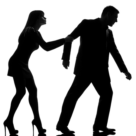 one caucasian couple dispute separation man leaving and woman holding back in studio silhouette isolated on white background photo