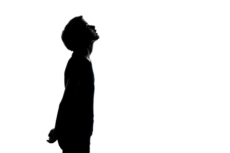 looking  up: one caucasian young teenager silhouette boy or girl looking up portrait in studio cut out isolated on white background Stock Photo