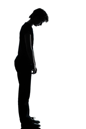 one caucasian young teenager silhouette boy or girl sad looking down  full length in studio cut out isolated on white background photo
