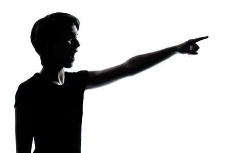 one caucasian young teenager silhouette boy or girl pointing surprised  portrait in studio cut out isolated on white background photo