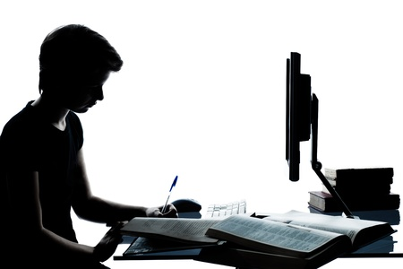 one caucasian young teenager silhouette boy or girl studying with computer computing laptop in studio cut out isolated on white background photo