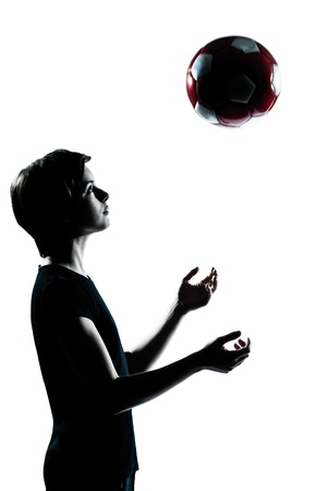 one caucasian young teenager silhouette boy girl tossing soccer football portrait in studio cut out isolated on white background photo