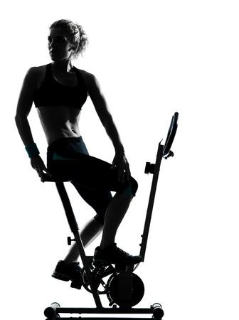 isol� sur fond blanc: une femme exer�ant le v�lo d'entra�nement de remise en forme posture exercice a�robie en studio isol� sur fond blanc