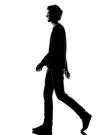 young man smiling walking silhouette in studio isolated on white background photo