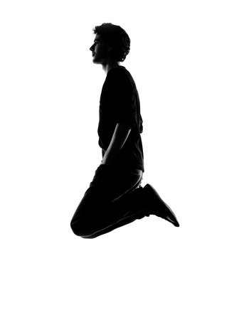 young man funny jumping silhouette in studio isolated on white background photo