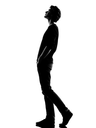 young man  walking looking up silhouette in studio isolated on white background photo