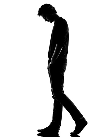 man looking out: young man sad walking silhouette in studio isolated on white background