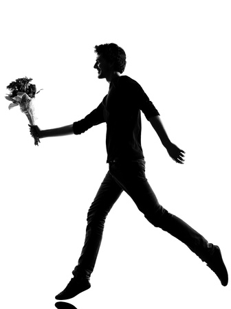 young man offering flowers bouquet silhouette in studio isolated on white background photo