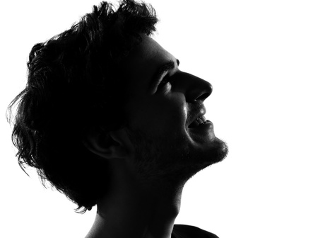 shadow face: young man looking up portrait silhouette in studio isolated on white background