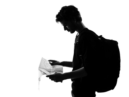 young man backpacker traveler looking at map silhouette in studio isolated on white background photo
