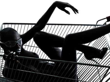 modelo desnuda: un hermoso negro mujer africana desnuda sentada en el interior de un carro de compras caddie en el estudio aislado sobre fondo blanco Foto de archivo