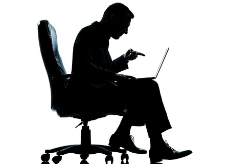 one caucasian business man computer computing pointing sitting in armchair silhouette Full length in studio isolated on white background photo