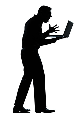 one caucasian business man computing computer laptop angry displeased silhouette standing Full length in studio isolated on white background photo