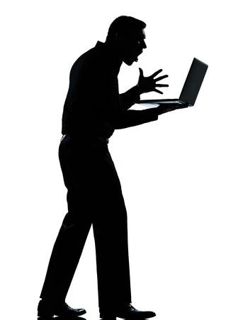 anger: un hombre de negocios cauc�sico de computaci�n port�til enojada silueta descontento de pie de cuerpo entero en el estudio aislado sobre fondo blanco