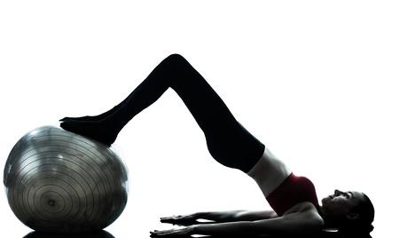 ein kaukasischen Frau, die Ausübung Fitness-Ball in der Silhouette Studio isoliert auf weißem Hintergrund
