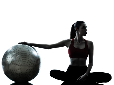 one caucasian woman exercising fitness ball in silhouette studio isolated on white background