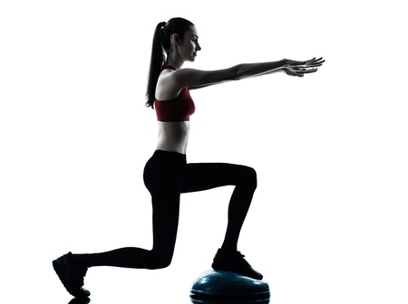 crouches: one caucasian woman exercising bosu balance ball trainer in silhouette studio isolated isolated on white background Stock Photo