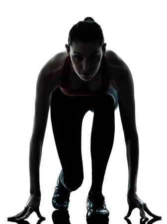 runner silhouette: one caucasian woman sprinter on starting block in silhouette studio isolated on white background Stock Photo