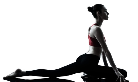 stretching: one caucasian woman exercising yoga in silhouette studio isolated isolated on white background