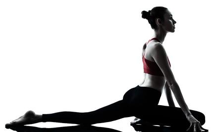 estiramientos: una mujer de raza cauc�sica ejercicio de yoga en el estudio de la silueta aislados sobre fondo blanco Foto de archivo