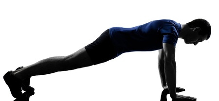 push ups: man exercising workout fitness aerobics posture in silhouette studio isolated on white background Stock Photo