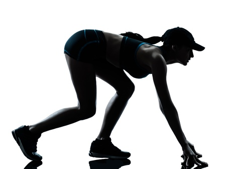 joggers: one caucasian woman runner jogger  on the starting block in silhouette studio isolated on white background Stock Photo