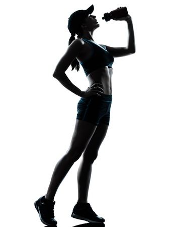 hydrate: one caucasian woman runner jogger drinking in silhouette studio isolated on white background