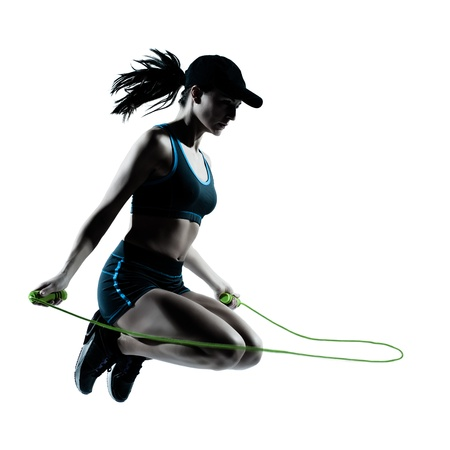 exercising: one caucasian woman runner jogger jumping rope in silhouette studio isolated on white background
