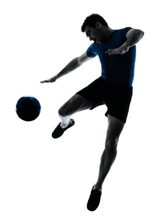 futbolista: un hombre caucásico volar patadas jugando al fútbol silueta de jugador de fútbol en el estudio aislado sobre fondo blanco Foto de archivo