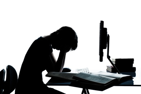 desperate: one caucasian young teenager silhouette boy or girl studying with computer computing laptop tired sad despair in studio cut out isolated on white background