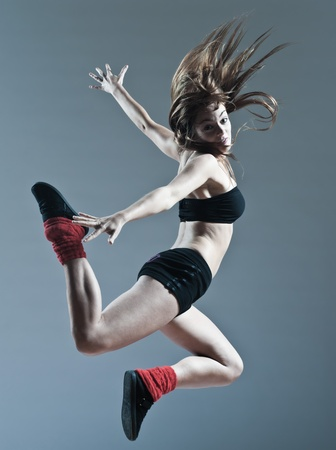 dancing pose: beautiful young caucasian woman girl dancer ballet breakdance leap jump on studio isolated background
