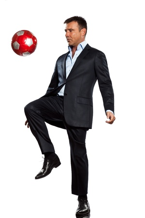 indoor soccer: one caucasian business man playing juggling soccer ball in studio isolated on white background