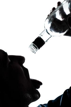 alcoholismo: un retrato de hombre caucásico silueta borracha Puring Botlle de alcohol vacías en el estudio de fondo blanco aisladas Foto de archivo
